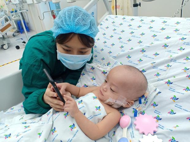 Ảnh: Hai chị em Trúc Nhi - Diệu Nhi tươi cười xem điện thoại, cầm bình sữa uống hết sau 18 ngày phẫu thuật-4