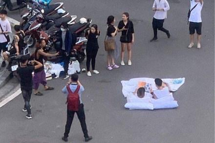 Đôi bạn trẻ bày gối, trải chăn nằm đọc sách ngay giữa quảng trường bất chấp xe cộ qua lại khiến dân mạng cực kỳ tranh cãi