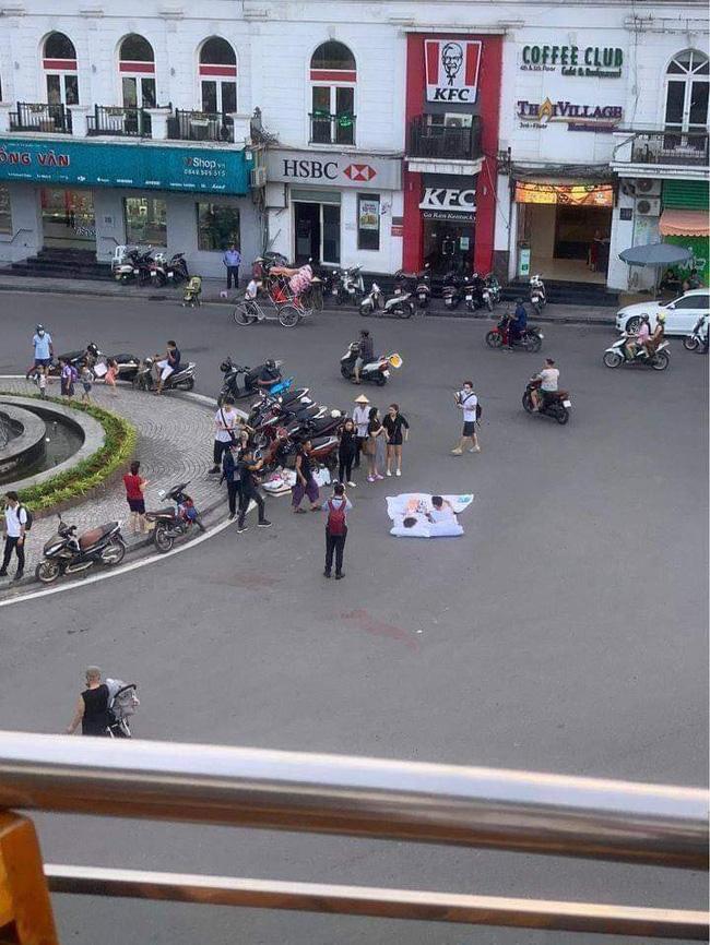Đôi bạn trẻ bày gối, trải chăn nằm đọc sách ngay giữa quảng trường bất chấp xe cộ qua lại khiến dân mạng cực kỳ tranh cãi-1