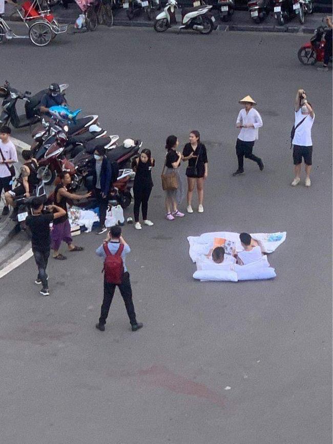Đôi bạn trẻ bày gối, trải chăn nằm đọc sách ngay giữa quảng trường bất chấp xe cộ qua lại khiến dân mạng cực kỳ tranh cãi-2