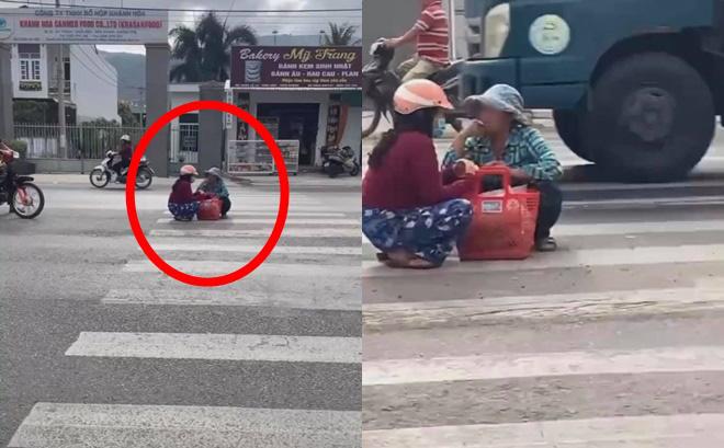 Mặc kệ xe cộ qua lại, 2 người phụ nữ ngồi xổm giữa đường buôn chuyện với nhau-1