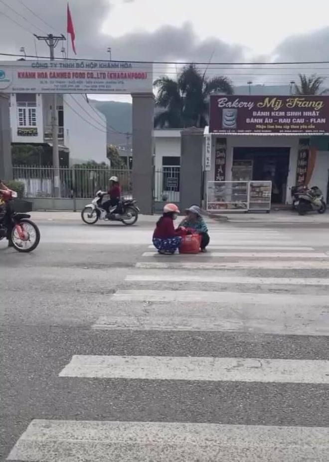 Mặc kệ xe cộ qua lại, 2 người phụ nữ ngồi xổm giữa đường buôn chuyện với nhau-2
