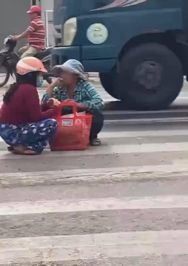 Mặc kệ xe cộ qua lại, 2 người phụ nữ ngồi xổm giữa đường buôn chuyện với nhau-3