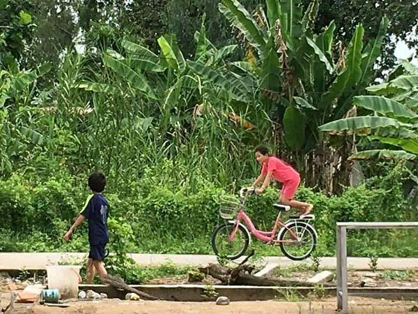 Bé gái đu hẳn người trên xe đạp như làm xiếc, nghịch ngợm thế này các mẹ cũng chào thua-2